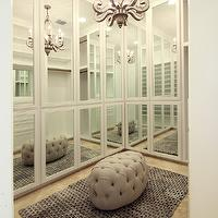 Marie Flanigan Interiors - closets - chic closet, mirrored doors, walk-in closet, master closet, hers closet, travertine tiled floors, travertine floors, tufted gray ottoman, oval tufted ottoman, gray rug, mirrored closet doors, antiqued mirrored chandelier, mirrored chandelier, modern closet, recessed lighting, pot lights, mirrored doors,
