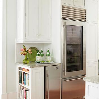 BHG - kitchens - all white kitchen, white kitchen cabients, shaker style cabinets, shaker cabinets, hardwood floors, granite countertops, stainless steel fridge, glass fronted stainless steel fridge, freezer drawer, mini fridge, stainless steel mini fridge, wine fridge, white subway tile, subway tile, subway tiled backsplash, ceiling height cabinetry, crown molding, cook book storage, cook book shelf, end cabinets, kitchen end cabinets, kitchen bookcases, cook book bookcase,