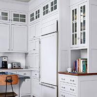 BHG - kitchens - white kitchen, soapstone counter, soapstone on kitchen island, carrara marble countertops, carrara marble, stained mahogany countertops, shaker cabinets, hidden fridge, hidden refrigerator, cabinet cover fridge, white subway tile, white subway tiled backsplash, subway tiled backsplash, marble countertops, stained wood countertops, black countertops, hardwood floors, hardwood floors in kitchen, nickel hardware, vintage barstool, iron and wood bar stool, industrial style barstool, beadboard ceiling, cook book niche, u-shaped kitchen, cabinets to ceiling, all white kitchen, bright white kitchen cabinets, corbel detail on island, wood covered refrigerator, wood paneled fridge, wood paneled refrigerator,