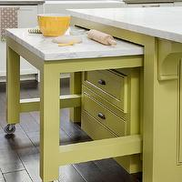BHG - kitchens - small kitchens, small kitchen island, space saving island, space saving kitchen island, pull out kitchen island, stowable kitchen island, roll out kitchen island, marble countertops, dark hardwood floors, green cabinetry, green kitchen island, avocado green, avocado green paint color, white perimeter cabinetry, farmhouse sink, subway tiled backsplash, subway tile, white subway tile, island on castors, yellow kitchen islands,
