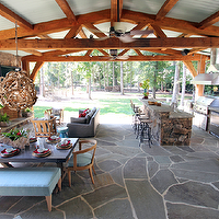 Lucy and Company - decks/patios - covered patio, rustic covered patio, slate pavers, natural slate paving, flagstone, slate pato, rustic wood beams, metal roof, tin roof, patio layout, functional patio layout, entertainers patio, covered patio for entertaining, porch swing, outdoor dining, zinc topped table, zinc topped outdoor table, modern teak furniture, outdoor furniture, teak patio furniture, blue upholstered bench, outdoor bench, stacked stone bar, outdoor kitchen, outdoor fireplace, fig tree, ficus tree, stacked stone, stone fireplace, outdoor fireplace with flat screen, gray outdoor sofa, driftwood pendant, twisted branch pendant, driftwood chandelier, outdoor entertaining, entertaining outdoors,