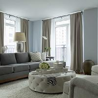The Elegant Abode - living rooms - blue and gray living rooms, blue living room walls, blue living room paint colors, living room paint colors, blue walls, floor to ceiling drapes, floor to ceiling taupe curtains, taupe curtains, taupe drapes, taupe window panels, rod drapes, taupe rod drapes, taupe rod curtains, taupe rod window panels, rod window panels, modern sofas, gray sofas, modern gray sofas, chevron pillows, white and gold chevron pillows, shag rugs, rugs with fringe, fringed rugs, fringe rugs, cream shag rugs, accent chairs, living room accent chairs, round ottomans, tufted ottomans, round tufted ottomans, ottoman coffee tables, zebra cowhide, west elm trays, west elm lacquer trays, west elm silver trays, antique mercury glass, mercury glass lamps, antique mercury glass lamps, sofa table lamps, oversized lamps, oversized table lamps,