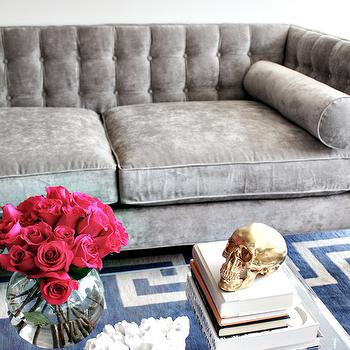 Made by Girl - living rooms - gray velvet sofas, modern gray velvet sofa, gray velvet bolster cushions, gray velvet bolster pillows, velvet sofa, modern velvet sofa, button tufted sofa, gray velvet button tufted sofa, blue rug, blue rug with greek key border, acrylic coffee table, white barnacles, stacked books, vase of roses, hot pink roses, brass skull, brass skull sculpture, white walls, abstract art, large scale abstract art, abstract art above sofa, greek key rugs, white and blue greek key rugs, gray sofa,