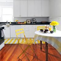 Rue Magazine - kitchens - white kitchen, white kitchen cabinets, white cabinets, black countertops, beadboard backsplash, white beadboard backsplash, black countertops, breakfast area, breakfast table, ceiling height cabinets, hardwood floors, yellow and white striped rug, yellow and white striped runner, yellow and white tablecloth, round table, round wooden table, round farmhouse style table, yellow chairs, yellow metal chairs, yellow metal folding chairs, paneled half walls, oven, brass hardware, brass cabinet hardware, pale gray walls, white and yellow kitchens, white and yellow kitchen rugs, yellow slat chairs, yellow dining chairs,