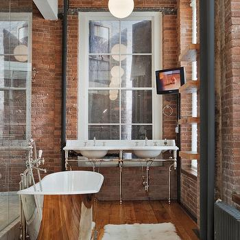 Jane Kim Design - bathrooms - exposed brick wall, red brick wall, brick wall, urban bathroom, large bathroom window, washstand in front of window, chrome based washstand, double sink washstand, walk-in shower, wood beams, rustic wood beams, glass shower, glass shower enclosure, cast iron bath tub, freestanding cast iron tub, oval cast iron bath, floor mounted faucet, hardwood floors, wood floors in bathroom, television in bathroom, rustic shelves, rustic wood shelves, silver bathtub, Mercer Bathtub, polished nickel Mercer bathtub, glass pendant, tv in bathroom, double washstand, wool rug, wool bath mat, rustic wood floors, rustic wood bathroom floors, marble washstand double, marble washstand, his and her sinks, glass shower partition, exposed brick walls in bathroom, bathroom exposed brick walls, bathroom TV, loft bathroom, urban archaeology washstand, , Urban Archaeology Washstand, Urban Archaeology Mercer Bathtub,