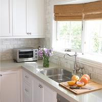 Brittany Stiles - kitchens - bay windows, kitchen bay windows, sink bay windows, kitchen sink bay windows, bamboo orman shades, stainless steel sink, stainless steel kitchen sink, vintage faucet, vintage kitchen faucet, white kitchen island, kitchen island, beadboard island, gray quartz countertops, shaker kitchen cabinets, beveled marble tiles, beveled marble subway tile, beveled marble subway tile backsplash, beveled marble kitchen tiles, sink next to dishwasher, dishwasher next to sink, kitchen crown moldings, cabinet crown molding, crown molding,