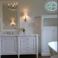 Giannetti Home - bathrooms - off-white walls, off-white paint colors, porthole window, porthole shaped window, bathroom window, bathroom porthole mirrors, creamy white cabinets, bathroom cabinets, beadboard cabinet, bathroom beadboard cabinet, bathroom vanity, white bathroom vanity, calcutta gold marble, calcutta gold marble countertop, calcutta gold marble backsplash, vanity mirror, bathroom vanity mirror, white vanity mirror, beveled mirror, white beveled mirror, freestanding tub, cream walls, cream paint, cream paint color, cream wall paint,