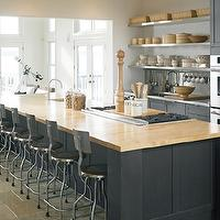 Charcoal gray kitchen cabinets paired with stainless steel perimeter countertops ...