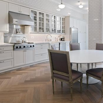 Paul Davis New York - kitchens - herringbone floor, hardwood floors in herringbone pattern, herringbone patterned hardwood floors, white Saarinen Table, modern white table, Saarinen Table, french dining chairs, plum colored french dining chairs, purple french dining chairs, stainless steel fridge, stainless steel double oven, farmhouse sink, gooseneck faucet, bridge faucet, gooseneck bridge faucet, apron sink, stainless steel dishwasher, linear kitchen, shaker cabinets, white shaker cabinets, glass fronted upper cabinetry, white subway tile, white subway tiled backsplash, subway tiled backsplash, subway tiled kitchen, marble countertops, school house lighting, school house pendants,