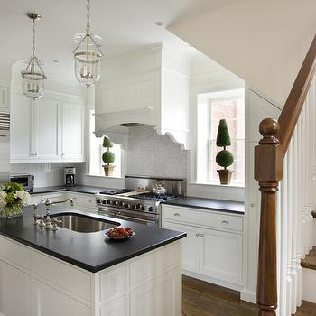 Kate Coughlin Interiors - kitchens - white shaker cabinets, shaker kitchen cabinets, cabinets above refrigerator, cabinets over refrigerator, black countertops, black kitchen countertops, stainless steel refrigerator, glass lanterns, kitchen island lanters, kitchen island sink, wood panel hood, wood panel kitchen hood, wood kitchen hood, kitchen windows, topiaries, kitchen topiary, mosaic marble backsplash, mosaic marble kitchen backsplash, mosaic marble tile kitchen, oak kitchen floors, oak hardwood floors, kitchen hardwood floors,