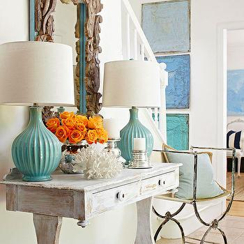 BHG - entrances/foyers - coastal entryway, beachy entryway, distressed white console, whitewashed console, distressed whitewashed console, driftwood mirror, beachy mirror, turquoise glazed lamps, turquoise lamps, turquoise table lamps, tiled floor, tiled entryway floor, white walls, antique iron chair, blue pillow, orange roses, silver candle holder, coral, blue wall art, turquoise wall art, weathered console table, whitewashed console table, white washed console table, foyer design, entrance, turquoise and gray foyer, gray and turquoise foyer,