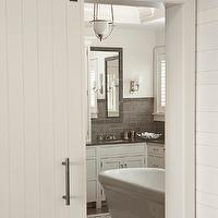 Shelter Interiors LLC - bathrooms - white and gray bathroom, white walls, white bathroom walls, gray tiled floor, gray tile bathroom floor, white bathroom cabinets, gray quartz countertops, gray tiled mirror, gray bathroom mirrors, white bathroom vanity, freestanding tub, bathtub in center of room, tub in center of room, bathtub in center of bathroom, tub in center of bathroom, inset tiles, mosaic marble tiles, mosaic marble inset tiles, bathroom doors, barn doors, bathroom barn doors, bathroom sliding barn doors, sliding barn bathroom door, barn bathroom door,