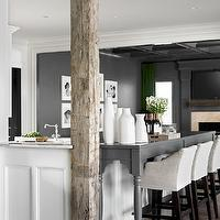 Melanie Turner Interiors - kitchens - recessed cabinetry, white recessed cabinetry, l-shaped peninsula, extended bar, extended bar peninsula, gray turned leg bar, turned leg bar, extended kitchen bar, white cabinetry, marble countertops, rustic wood beams, rustic beam, rustic wood column, wood beams, wood column, exposed beam, exposed wood column, hardwood floors, slipcovered barstools, linen slipcovered bar stools, woven tray, white vases, ceramic white vases, charcoal gray wall color, gray wall color, dark gray wall color, open plan kitchen, open plan, recessed lighting, pot lights, rustic beams, rustic wood beams,
