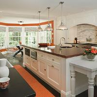 Shelter Interiors LLC - kitchens - white and orange kitchen, kitchen with orange accents, kitchen with pops of yellow, curved kitchen hood, wood kitchen hood, cooktop alcove, kitchen alcove, white kitchen cabinets, white shaker cabinets, spice racks, pull out spice racks, cooktop spice racks, linear marble tiles, linear marble tile backsplash, linear marble cooktop backsplash, wood refrigerator, wood freezer drawers, wood panel fridge, black perimeter countertops, black countertops, black kitchen countertops, large center island, large kitchen island, butcher block countertop, butcher block top, butcher block island, butcher block kitchen island, kitchen island prep sink, island prep sink, industrial island pendants, kitchen island pendants, microwave nook, kitchen island microwave, baking island, marble baking island, baking kitchen island, marble top baking island, turned legs, island with turned legs, farmhouse sink, orange runners, kitchen runners, orange kitchen runners, bay windows, kitchen bay windows, bay windows in kitchen, dining nook, blue and orange shades, blue and orange roman shades, x base dining table, x dining table, bertoia chairs, orange accents, orange kitchen accents,
