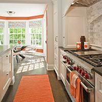 Shelter Interiors LLC - kitchens - white and orange kitchen, kitchen with orange accents, kitchen with pops of yellow, curved kitchen hood, wood kitchen hood, cooktop alcove, kitchen alcove, white kitchen cabinets, white shaker cabinets, spice racks, pull out spice racks, cooktop spice racks, linear marble tiles, linear marble tile backsplash, linear marble cooktop backsplash, black countertops, black kitchen countertops, orange runners, kitchen runners, orange kitchen runners, bay windows, kitchen bay windows, bay windows in kitchen, dining nook, blue and orange shades, blue and orange roman shades, x base dining table, x dining table, bertoia chairs,