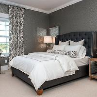 Atmosphere Interior Design - bedrooms - blue and gray bedroom, blue and gray master bedroom, contemporary gray wallpaper, gray and silver wallpaper, dark blue upholstered bed, dark blue tufted bed, tufted dark blue bed with nailhead trim, white bedding, white hotel bedding, black and white hotel bedding, black and white bolster pillow, oatmeal colored carpet, wall to wall carpet, beveled mirror, mirrors above nightstands, glass table lamp, mirror nightstands, mirror paneled nightstands, barrel back chair, black piping, black and white floral drapes, polished nickel accent table, chic blue and gray bedroom, silver wallpaper, metallic wallpaper,