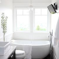 Pure by Ami Mckay - bathrooms - white bathroom, black and white bathroom, freestanding tub, bath under window, bath tub under window, crystal pendant, crystal pendant over bath, tv in bathroom, flat screen tv over bath tub, white walls, wainscoting, wainscoting in bathroom, black marble tiled floors, marble tiled floors, black marble floor tiles, espresso stained vanity, contemporary bathroom, rectangular vessel sink, marble countertops, marble topped vanity, floor mounted faucet, modern floor mounted faucet, polished nickel floor mounted faucet, egg tub, egg bathtub, egg shaped tub, egg shaped bathtub,