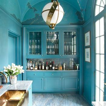 Architectural Digest - kitchens - turquoise walls, turquoise blue walls, turquoise kitchen, turquoise blue kitchen, wet bar, wet bar cabinets, glass front cabinets, glass front kitchen cabinets, turquoise cabinets, turquoise blue cabinets, turquoise kitchen cabinets, turquoise blue kitchen cabinets, marble countertops, marble backsplash, slab backsplash, marble slab backsplash, vaulted ceiling, kitchen vaulted ceiling, kitchen with vaulted ceiling, painted ceiling, painted kitchen ceiling, constellation ceiling, constellation painted ceiling, copper sink, copper kitchen sink, kitchen floors, kitchen floor draining system, zodiac pendant, zodiac chandelier, blue kitchen, blue kitchen cabinets, Visual Comfort Lighting Zodiac Pendant,
