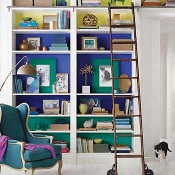 Martha Stewart - dens/libraries/offices - color blocking, color blocked, color blocked bookshelves, color blocked built ins, color blocked bookcase, built ins, built in bookcase, painted backs of shelves, painted bookcases, painted built-ins, rustic library ladder, library ladder on wheels, wheeled library ladder, color blocked shelves, color blocked shelving, color blocked bookcase, color blocked built-ins, french chair, wingback chair, french wingback chair, teal chair, teal wingback chair, teal french chair, teal french wingback chair, purple throw, vintage floor lamp, plank floors, white plank floors, white painted floors, white wood floors,