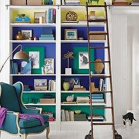 Martha Stewart - dens/libraries/offices - Benjamin Moore - Scandinavian Blue - color blocking, color blocked, color blocked bookshelves, color blocked built ins, color blocked bookcase, built ins, built in bookcase, painted backs of shelves, painted bookcases, painted built-ins, rustic library ladder, library ladder on wheels, wheeled library ladder, color blocked shelves, color blocked shelving, color blocked bookcase, color blocked built-ins, french chair, wingback chair, french wingback chair, teal chair, teal wingback chair, teal french chair, teal french wingback chair, purple throw, vintage floor lamp, plank floors, white plank floors, white painted floors, white wood floors,