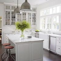 Architectural Digest - kitchens - light filled kitchens, bank of windows, kitchen windows, kitchen with bank of windows, bank of windows in kitchen, twin dishwashers, dual dishwashers, dishwashers flanking sink, farmhouse sink, bridge faucet, glass front cabinets, upper cabinets, upper kitchen cabinets, lower kitchen cabinets, top cabinets, base cabinets, raised panel cabinets, white kitchen cabinets, traditional kitchen cabinets, marble countertops, center island, kitchen island, kitchen island storage, kitchen island with drawers, swivel stools, industrial stools, brushed nickel pendants, industrial pendants, hardwood floors in kitchen, bar stools, barstools, industrial barstools,