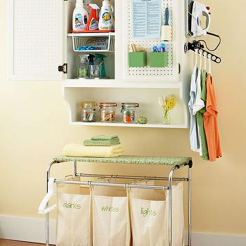 BHG - laundry/mud rooms - laundry room storage, hardwood floors, white baseboards, yellow walls, yellow wall color, laundry room, organized laundry room, laundry room organization, laundry room cupboard, divided laundry hamper, monogrammed laundry hamper, laundry hamper on castors, hanging rail, drying rail, iron holder, laundry room, laundry room design, laundry room bins, laundry bins, laundry sorter, laundry room sorter, laundry bin ideas, laundry room bin ideas, laundry sorter ideas, laundry room sorter ideas,