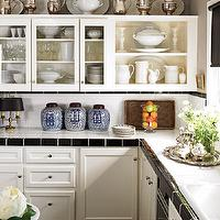 House Beautiful - kitchens - Benjamin Moore - Brilliant White - small kitchen, small chic kitchen, subway tile countertops, subway tile backsplash, black border tiles, black subway tile, black border tiles, cream cabinets, cream kitchen cabinets, glass front cabinets, glass front kitchen cabinets, overlay cabinets, cream overlay cabinets, overlay kitchen cabinets, chinese ginger jars, ginger jars, sterling silver platters, sterling silver pitchers, sterling silver urns,