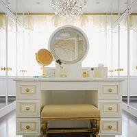 Elle Decor - closets - gauzy window sheers, walk-in closet, glamorous walk-in closet, glamorous closet, hardwood floors, mirror fronted closet doors, mirrored closet doors, gold and crystal chandelier, ornate gold and crystal chandelier, crystal chandelier in closet, mother-of-pearl inlay, mother-of-pearl inlaid vanity, white vanity, glamorous vanity, make-up vanity, white make-up vanity, crystal chandelier, make-up mirror, gold make-up mirror, gold legged stool, gold stool, upholstered stool with gold legs, vanity with built-in mirror, white and yellow closet, closet vanity, white and yellow vanity, vanity bench, vanity ottoman, gold vanity bench, gold vanity ottoman,