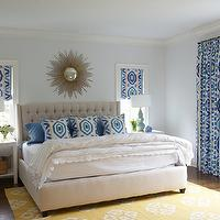Nightingale Design - bedrooms - yellow and blue bedroom, blue and yellow bedroom, blue bedroom with pops of yellow, yellow accents, blue and yellow room, yellow and blue room, blue walls, blue bedroom walls, prospect fabric, ikat curtains, ikat drapes, ikat window panels, ikat window treatments, blue and yellow curtains, blue and yellow drapes, blue and yellow window panels, blue and yellow ikat curtains, blue and yellow ikat drapes, ikat roman shades, blue and yellow roman shades, blue and yellow ikat roman shades, sunburst mirror, gold sunburst mirror, gray headboard, tufted headboard, gray tufted headboard, blue and yellow pillows, ikat pillows, blue and yellow ikat pillows, scallop duvet, scalloped duvet, scalloped bedding, white nightstands, parsons nightstands, white parsons nightstands, turquoise lamp, turquoise blue lamps, yellow rug, andalusian rug, yellow andalusian rug, yellow accents, yellow accents, thom filicia fabric, ikat window panels, Thom Filicia Prospect Fabric in Lake, West Elm Andalusian Rug,