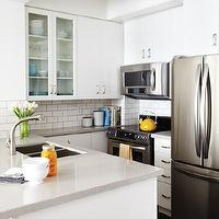 House & Home - kitchens - all-white kitchen cabinets, white kitchen cabinets, modern kitchen cabinets, white kitchen cabinets, white kitchen cabinetry, gray counters, gray countertops, gray quartz counters, gray quartz countertops, quartz countertops, stainless steel oven, stainless steel fridge, marble subway tiled backsplash, marble subway tiled, dolomite marble, dolomite marble subway tile, gray grout, darker grout, contrasting grout, built-in microwave, stainless steel microwave, u-shaped kitchen, kitchen peninsula, peninsula island, peninsula bar, undermount sink, modern faucet, glass fronted accent cabinet, overhead microwave, grey countertops,