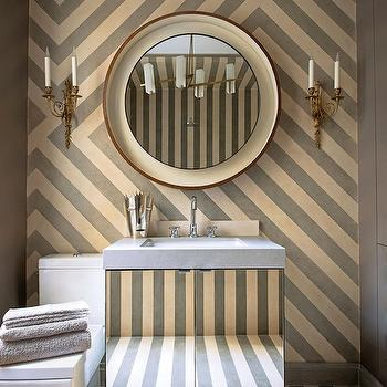 bathrooms - chic powder room, striped powder room, cream and gray powder room, gray walls, mirrored vanity, mirrored bathroom vanity, mirrored washstand, mirrored cabinets, mirrored bathroom cabinet, gray countertop, convex mirror, round mirror, round powder room mirror, french sconces, brass sconces, brass french sconces, striped accent wall, accent wall, powder room accent wall, striped floor, cream and gray floor, striped powder room floor,