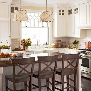 BHG - kitchens: traditional kitchen, white kitchen cabinets, off white cabinets, off white kitchen cabinets with glass fronted accent panel, l-shaped kitchen, subway tiled backsplash, white subway tiled backsplash, stainless steel oven, hardwood floors, kitchen island, gooseneck faucet, bridge faucet, bridge gooseneck faucet, apron sink, farm sink, farmhouse sink, stained wood countertops, stained wood counters, x-backed barstools, wooden x-backed bar stools, granite counters, granite countertops, Grosvenor Pendants,