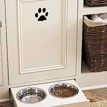 BHG - kitchens - all-in-one pet station, sliding drawer with feeding bowls, hidden pet food bowls, pet lovers kitchen, toe-kick drawer, toe-kick drawer storing pet bowls, ivory painted recessed cabinets, ivory kitchen cabinets, paw print, woven storage baskets, storage basket cubbies, rattan storage baskets, tiled floors, jute are rug, hidden pet food bowls, hidden pet bowl station,
