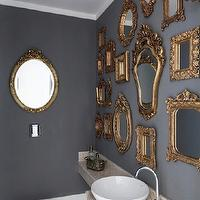 bathrooms - eclectic bathroom gilt ornate mirrors, ornate gilt mirrors, gold ornate mirrors, ornate gold mirrors, collection of mirrors, wall of mirrors, gallery of mirrors, modern toilet, floating vanity, floating bathroom vanity, floating sink, floating bathroom sink, white bowl sink, bowl vessel sink, gooseneck faucet, modern gooseneck faucet, slate gray walls, slate gray bathroom walls, blue and gold bathroom,