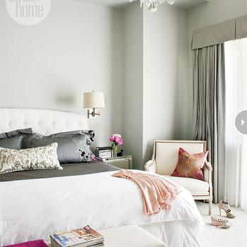 Style at Home - bedrooms - white headboard, white tufted headboard, white button tufted headboard, white diamond button tufted headboard, white duvet, hot pink throw, upholstered bench, wall to wall carpet, ivory carpet, adjustable wall sconce, brushed nickel adjustable wall scones, gray green walls, oversized glass and crystal chandelier, vaulted ceiling, gray green drapes, gray green curtain, pleated valance, gray drapes, gray curtains, gray silk pillows, mirrored nightstand, bergere chair, french chair, french bergere chair, gray coverlet, silk floral pillow, peach patterned pillow, pretty bedroom, feminine bedroom,