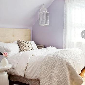 Style at Home - bedrooms: pretty bedroom, feminine bedroom, lavender wall color, lilac wall color, floral chandelier, floral chandelier with crystal droplets, modern tufted headboard, oatmeal button tufted headboard, button tufted headboard, white bedding, white bed linens, white duvet, white pillows, diamond pleated accent pillow, diamond pleated pillow, ivory matelasse coverlet, matelasse coverlet, white ornamental birdcage, ornamental birdcage, gauzy drapes, gauzy curtains, hardwood floors, sheepskin rug, Martini Side Table, lavender and tan bedroom,