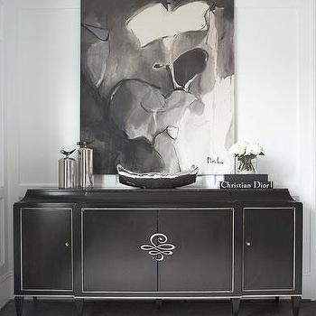 Linda McDougald Design - entrances/foyers - chic black and white foyer, black and white foyer, dark hardwood floors, hardwood floors, black cabinet, black cabinet with silver inlaid door panels, black and silver cabinet, black white and gray canvas, black white and gray abstract, abstract art, white walls, paneled walls, wainscoting, mill work, white wainscoting, white inset paneled walls, silver canisters, tall silver canisters, black and silver bowl, stacked books, vase of white roses, glamorous foyer, white recessed panel wainscoting, gray and white rug, gray and white geometric rug, black credenza,