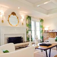 Evars and Anderson - living rooms: coffered ceiling, recessed coffered ceiling, coffered tray ceiling, wainscoting paneled fireplace, traditional fireplace, white slipcovered armchairs, white armchairs, emerald green pillows, green pillows, industrial coffee table, iron based wood topped coffee table, white candlesticks, white candlestick holders, antique chest, upholstered bench, palm frond patterned curtains, palm frond patterned drapes, floor to ceiling drapes, ceiling height drapes, oval mirror, oval gilt mirror, brass wall sconces, contemporary wall sconces, contemporary brass wall sconces, ivory wall color, creamy white wall color, emerald green and white living room, white and green living room,