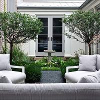 Northworks Architects - decks/patios - backyard courtyard, courtyard, bird sink, stone bird sink, gray french doors, flowers, trees, outdoor furniture, modern outdoor furniture, white outdoor furniture, white modern outdoor furniture, light gray cushions,