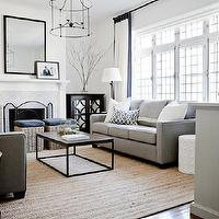 Lux Decor - living rooms: monochromatic living room, white walls, white wall color, recessed lighting, pot lights, traditional fireplace, marble mosaic fireplace, mini marble mosaic fireplace surround, mirror fronted cabinets, black mirror fronted cabinets, mirror fronted cabinets flanking fireplace, black mirror fronted chest, glass vase, branches in vase, black mirror, black framed mirror, iron floor lamp, gray rattan stools, gray sofa, contemporary gray sofa, white pillow, gray trellis pillow, fireplace screen, white drapes with solid black border, white drapes with black edge, white curtains with black border, white curtains with solid black edge, iron lantern pendant, large lantern pendant, large open lantern pendant, symmetrical living room, symmetrical living room arrangement, leaded glass french doors, coffee table, iron based coffee table, floor to ceiling drapes, floor to ceiling curtains, iron based wood topped coffee table, sisal rug, bound sisal rug, natural fiber rug, french doors, face to face sofas, sofas facing each other, modern gray sofas, gray sofa, black and white curtains, black and white drapes, black and white window panels,