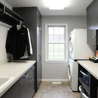 Mullet Cabinets - laundry/mud rooms - galley laundry room, narrow laundry room, long narrow laundry room, laundry room storage, laundry room cabinets, laundry room cabinetry, gray walls, gray wall color, tiled floors, black laundry room cabinets, deep white sink, laundry room sink, drying rail, drying rail in laundry room, clothes rail in laundry room, stackable washer and dryer, front loading washer and dryer, stackable front loading washer and dryer, laundry basket storage, laundry hamper storage, laundry basket cubbies, laundry hamper cubbies, frameless cabinets, frameless black cabinets,