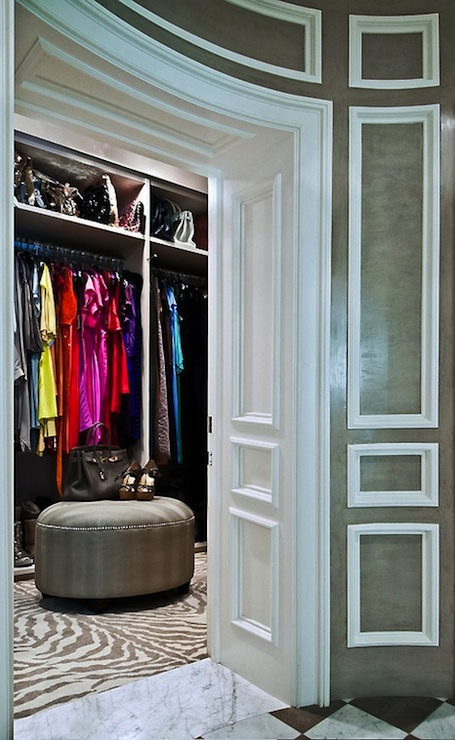 Sue Firestone - closets - chic walk-in closet, walk-in closet, master closet, glamorous closet, high end closet, raised panel wainscoting, paneled walls, marble floor, gray ottoman, round gray ottoman, round gray ottoman with nailhead trim, zebra rug, zebra print rug, brown and cream zebra print rug, floor to ceiling closet storage, upper handbag shelves, handbag shelves, chic closet, gray green wall color, wainscoting paneled walls, wainscoting,