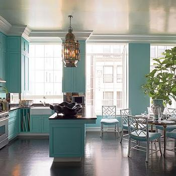 Harper's Bazaar - kitchens - turquoise kitchen, turquoise blue kitchen, turquoise kitchen cabinets, turquoise blue kitchen cabinets, crown molding, kitchen crown molding, kitchen molding, cabinet molding, cabinet crown molding, farmhouse sink, vertical shelving, open shelving, shelves for baking pans, baking pan shelves, vertical shelves, vertical shelving, turquoise kitchen peninsula, turquoise blue kitchen peninsula, honed black countertops, black countertops, decorative clam shell. black clam shell, round dining table, bamboo chair, faux bamboo chair, white bamboo chair, white faux bamboo chair, turquoise cushion, turquoise blue cushion, fiddle leaf fig, metallic ceiling,