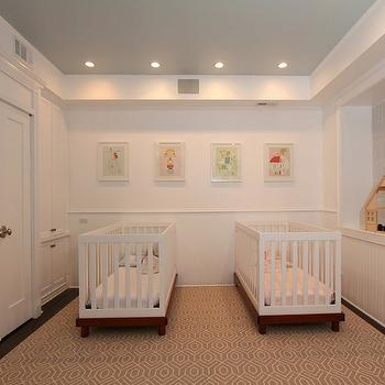 Design Build 4U Chicago - nurseries - twins nursery, twin nursery, twin nursery design, side-by-side cribs, modern cribs, modern white cribs, beadboard walls, beadboard half walls, recessed nook, wooden dolls house, nursery, built-in closets, built-in cupboards, wall of closets, nursery storage, recessed lighting, pot lights, dark hardwood floors, modern white crib, gray geometric rug, geometric rug, gray and ivory geometric rug, white walls, blue ceiling, sky blue ceiling, pearlescent blue ceiling, nursery art, framed nursery art,