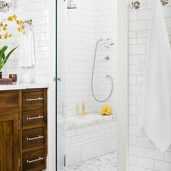 BHG - bathrooms - subway tile, white subway tile, white subway tiled shower enclosure, white subway tiled backsplash, subway tiled shower, shower bench, marble topped shower bench, polished chrome shower head, rainfall shower head, rain head shower, carrara marble floor, hexagonal marble floor tile, hexagonal carrara marble floor tile, glass shower door, towel hooks, towel ring, walk-in shower, walk-in shower enclosure, brown marble border, thin brown tiled border, walnut vanity, stained walnut vanity, walnut bathroom vanity, satin nickel hardware, polished nickel wall sconce, chocolate brown wall color, marble counters, marble countertops,