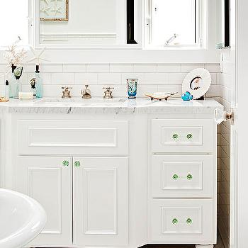 BHG - bathrooms - beach bathroom, beachy bathroom, white and green bathroom, coastal bathroom, nautical bathroom, white hexagonal floor tile, hexagonal floor tile, white subway tile, subway tile, white subway tiled backsplash, white subway tiled bathroom, green glass hardware, sea green glass hardware, marble counter, marble countertops, vintage style faucet, mirror flanked by windows, beachy blinds, fish patterned window blinds, green and ivory ocean patterned blinds, framed starfish, footed vanity, white vanity, white single vanity, white bathroom vanity, green glass pulls, green glass cabinet pulls, green glass cabinet hardware,