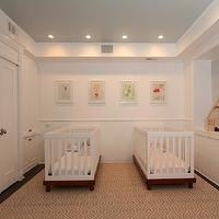 Sweet twins nursery with built-in closets and white beadboard wrapped walls. Four framed ...