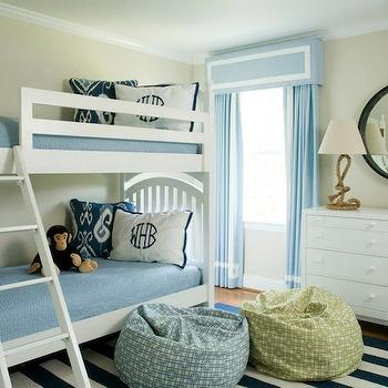 Liz Carroll Interiors - boy's rooms - boys room, boys bedroom, nautical style boys bedroom, striped navy blue and white rug, striped blue and white rug, beanbags, green geometric patterned beanbag, blue geometric patterned beanbag, white bunk beds, bunk beds, white dresser, round black framed mirror, rope lamp, rope table lamp, dog bookends, blue drapes, blue drapes with white ribbon trim, blue valance with white ribbon trim, blue curtains, blue curtains with white ribbon trim, monogrammed pillow, white pillow with blue monogram, blue ikat pillow, blue coverlet, blue blanket, beige walls, window valance, green bean bag, blue bean bag, spinnaker lamp, greek key curtains, green key drapes, blue greek key curtains, blue greek key drapes,