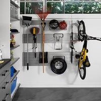 Transform Home - garages - organized garage, garage storage, garage workbench, epoxy garage floors, gray epoxy garage floors, workbench, brushed aluminium fronted doors, black formica counter, wall mounted track system in garage, garage workbench, well organized garage, garage storage system, aluminium fronted workbench, modern garage storage, well organized garage storage,