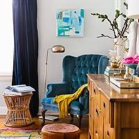 Emily Henderson - bedrooms - eclectic bedroom, vintage bedroom, eclectic vintage bedroom, navy blue curtains, navy blue drapes, dark blue curtains, dark blue drapes, dark blue window panels, floor lamp, vintage floor lamp, velvet chair, tufted chair, upholstered chair, wingback chair, blue upholstered chair, blue wingback chair, blue tufted chair, blue velvet chair, blue velvet tufted chair, blue velvet wingback chair, blue tufted wingback chair, yellow throw, yellow throw blanket, vintage leather ottoman, moroccan ottoman, pink and yellow rug, floral rug, pink and yellow floral rug, vintage dresser, turquoise accents, gold accents, light gray walls,